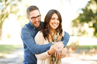 man holding woman from behind with both smiling